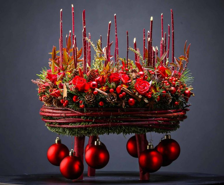 Christmas workshops are the most successful ones. Wreaths are traditional at this time of the year. Here it is special as the wreath has legs and not touching the table. Decorated with Christmas balls hanging under it. Typical christmas decoration on the top.