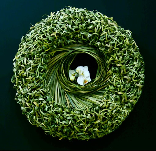 Big green wreath made from Typha grass which is knotted. Thousands of knots pinned on a wreath. The center of the wreath is decorated with a Phalaenopsis orchid.
