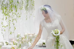 In the program of the EFDE bridalwork is very important. A romantic bride with a veil and a beautiful round bridal bouquet in her hand inspects the table decoration of her wedding feast