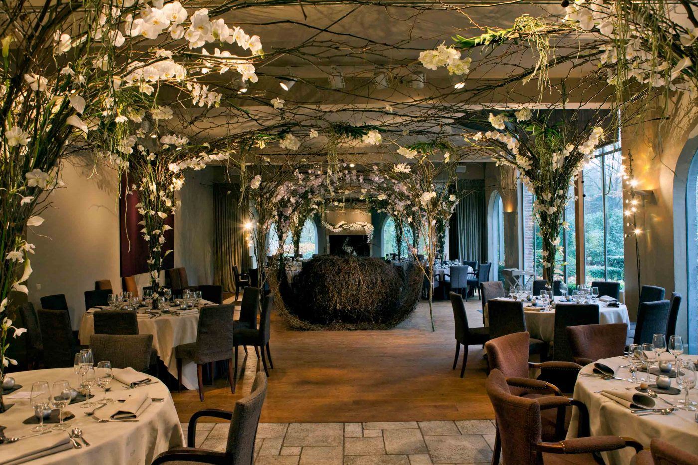Restaurant decoration with white flowers composed on the tables in a conical branch structure. At the ceiling they allcome together and decorate the whole room this way.
